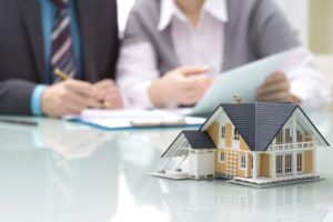 People sign home insurance papers