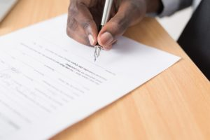 A person signs a title insurance document