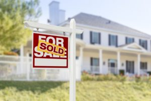 buying a home for sale sign